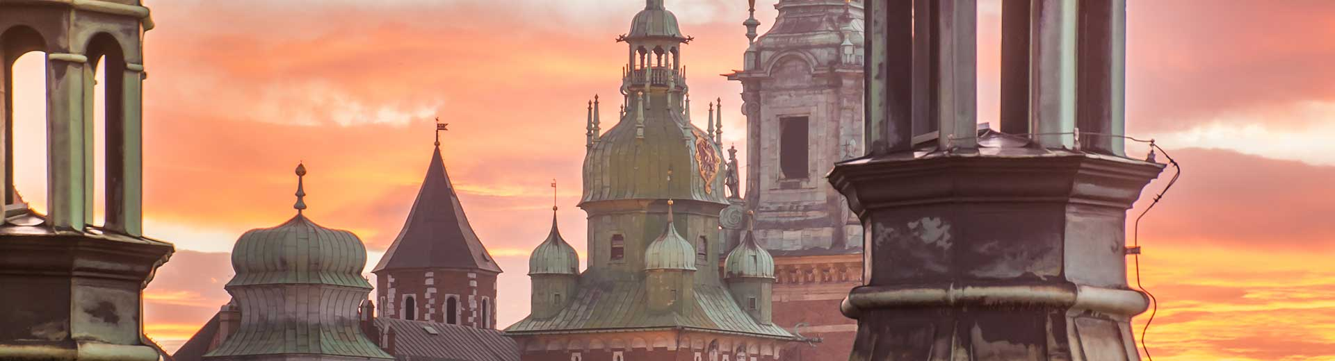 The spires of buildings in Krakow's Old Town at sunset