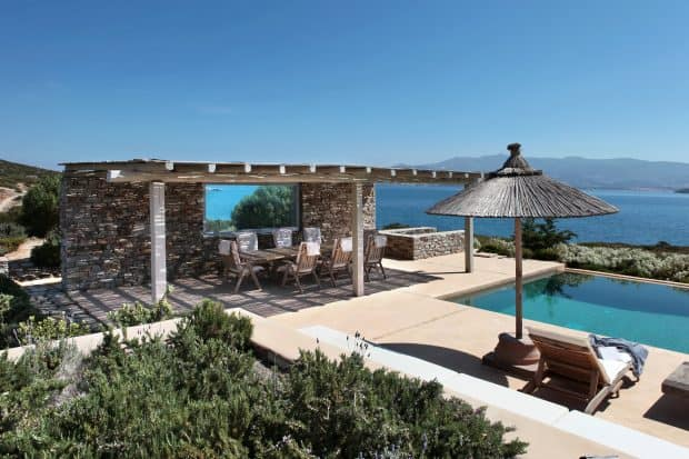 Outdoor area of a Greek island villa with swimming pool and sea view