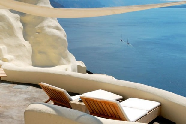 lounge chairs on patio overlooking ocean in Greece
