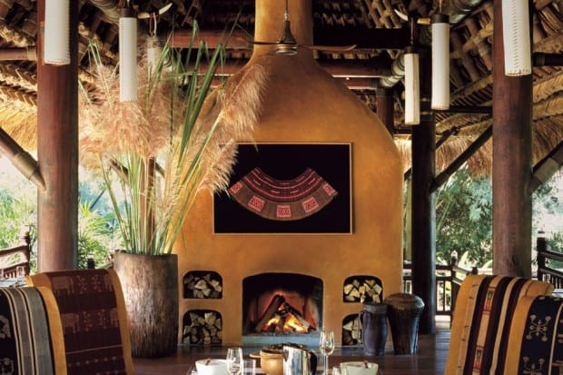 Outdoor dining table and fireplace at Four Seasons Golden Triangle Tented Camp in Thailand