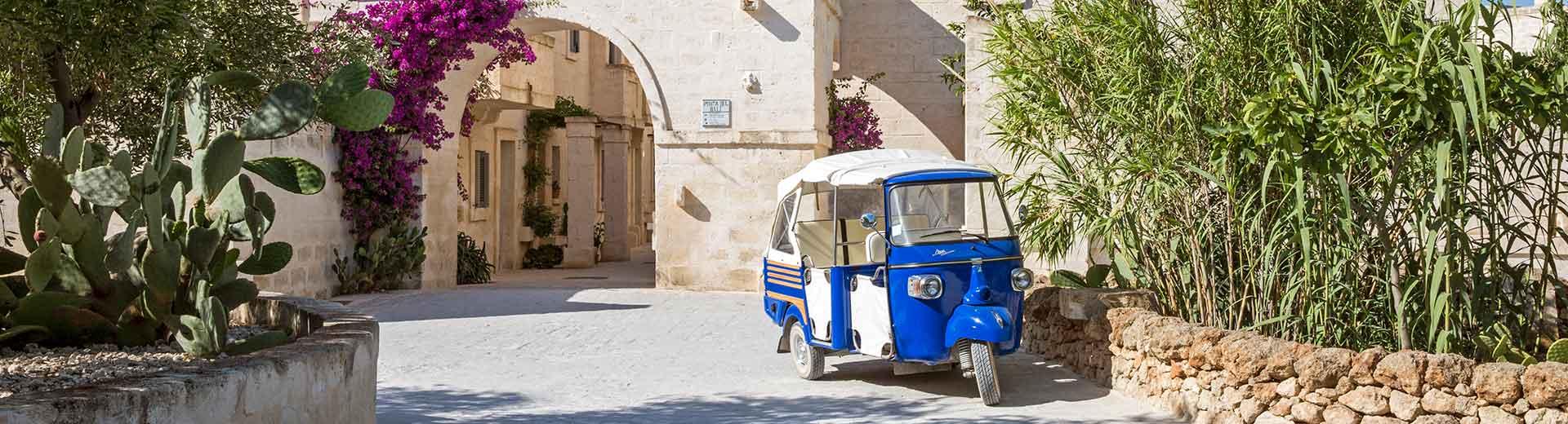 a old fashioned car outside of borgo egnazia hotel in puglia, italy