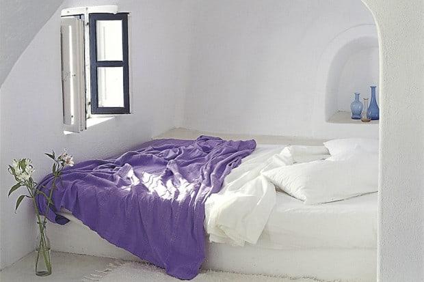 Bedroom with purple blanket in Perivolas hotel on Santorini Greece