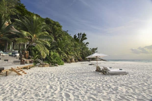 Beach with 2 lounge chairs and umbrella