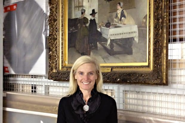 Karyn Millet in front of a Francis Davis Millet painting