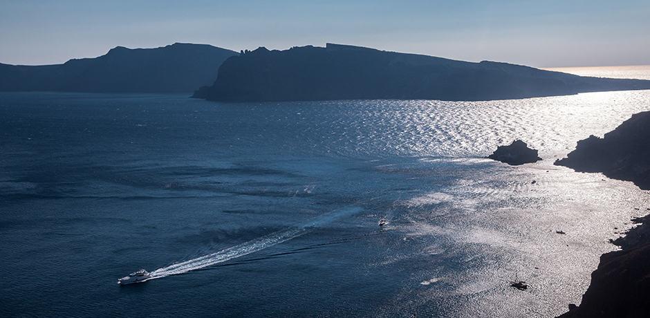 A boat putters through the caldera of Santorini