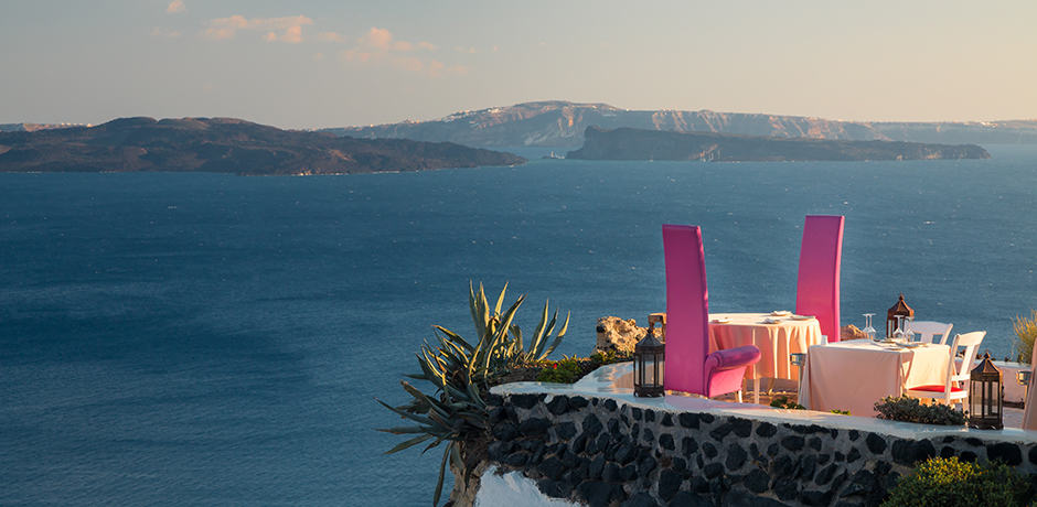 A romantic table overlooks the caldera at the restaurant of Andronis Boutique Hotel