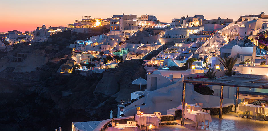 The sun sets over the white-washed cliffside town of Oia
