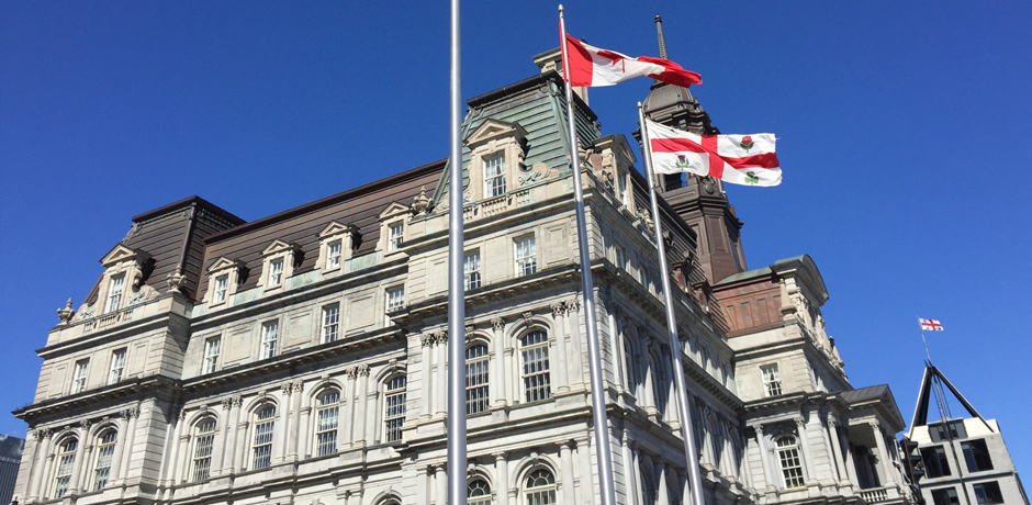 The flags of Quebec, Canada and Montreal fly adjacent to City Hall